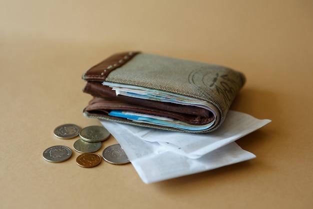 Vista laterale del portafoglio con monete in denaro e assegno circolare dal negozio