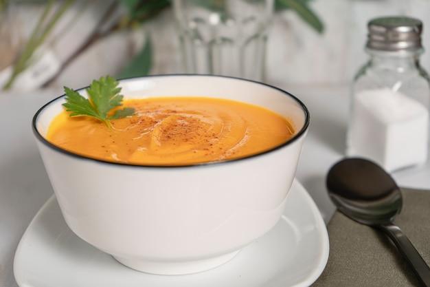 Vista laterale di una ciotola bianca con crema di zucca e carote