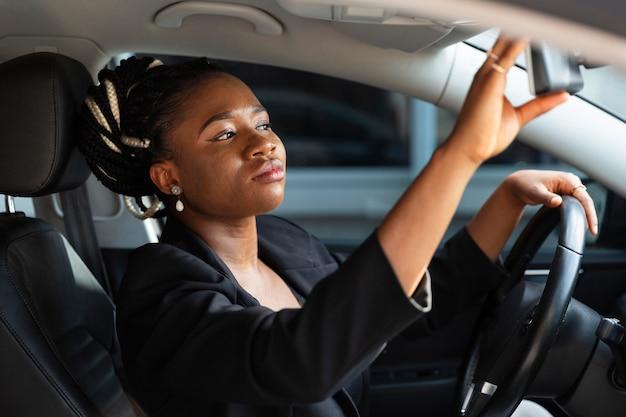 Vista laterale della donna che regola il suo specchio per auto