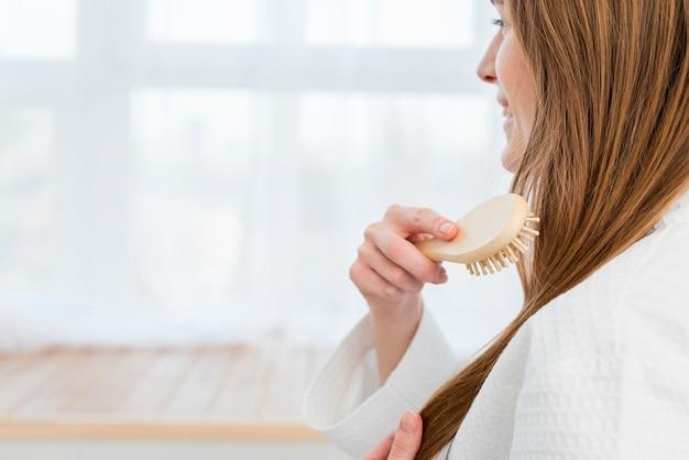 Vista laterale della donna che spazzola i suoi capelli