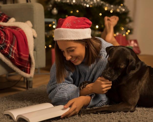 Vista laterale della donna sul libro di lettura di natale con il suo cane