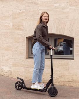 Vista laterale della donna in città su scooter elettrico