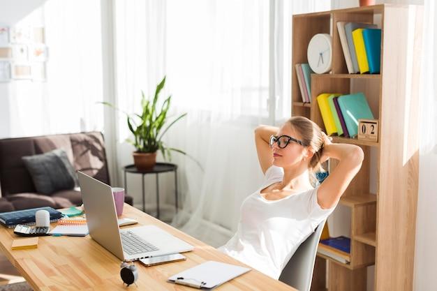 Vista laterale della donna allo scrittorio che lavora dalla casa