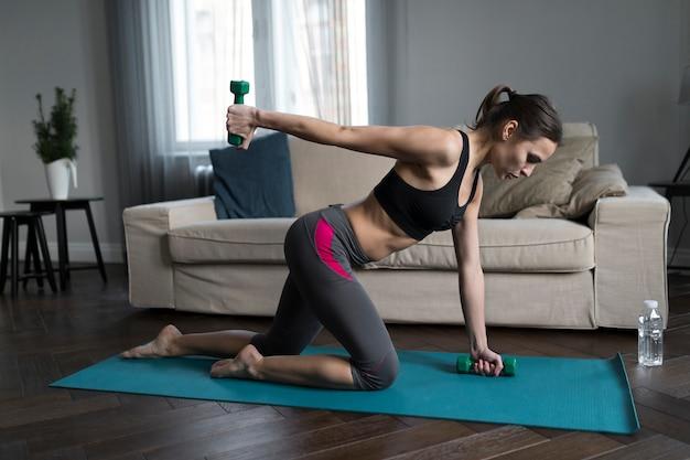 Vista laterale della donna che fa gli esercizi con i pesi a casa