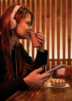 Donna di vista laterale che beve caffè