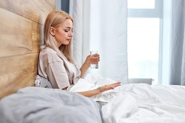 Vista laterale sulla donna che si sente male, va a bere acqua con farmaci in pillole, interno di casa, copia spazio. quella signora bionda che ha febbre, raffreddore o infezione da coronavirus. in camera da letto da solo