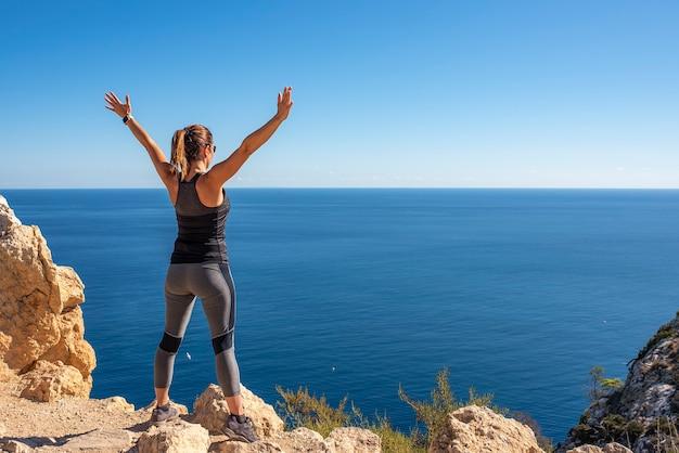 Vista laterale di una donna che si diverte durante una gita in montagna, in piedi sul ciglio della montagna, godendosi il suo panorama, a braccia aperte, in una giornata di sole []