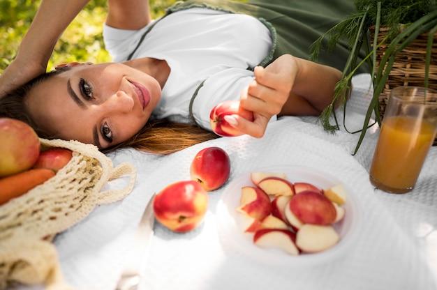 Donna di vista laterale che ha un picnic con cibo sano