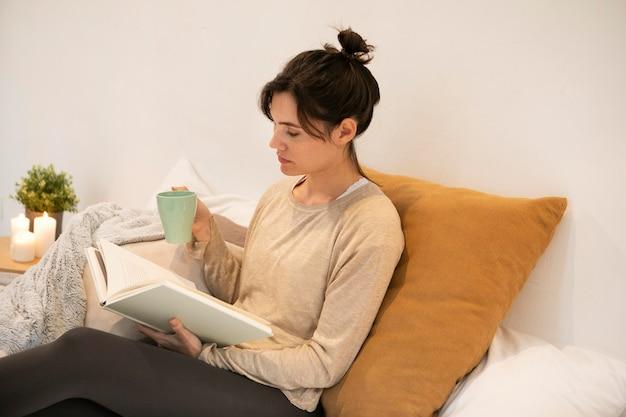 Donna di vista laterale che tiene una tazza di caffè e che legge un libro