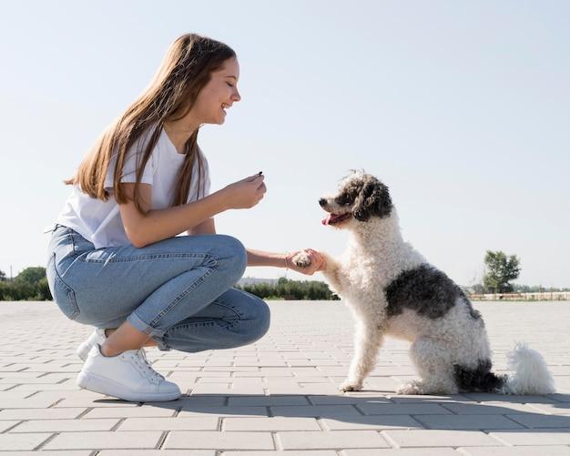Vista laterale della donna che tiene la zampa del cane