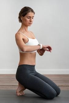 Vista laterale della donna a casa facendo yoga