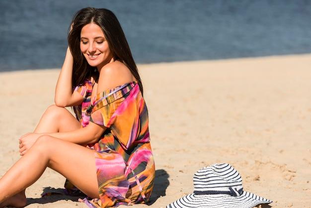 Vista laterale della donna in posa sulla spiaggia