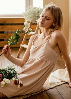 Vista laterale della donna in posa con i fiori di primavera Foto Premium