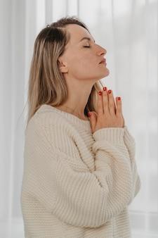 Vista laterale della donna che prega a casa
