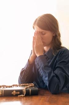 Vista laterale della donna che prega con il libro sacro e il rosario