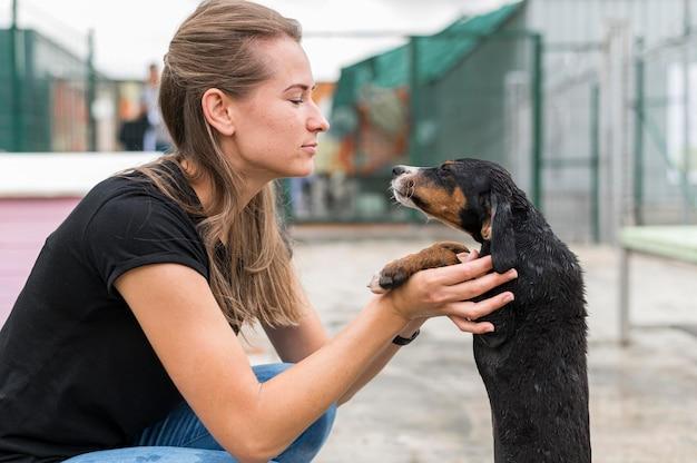 Vista laterale della donna e del cane da salvataggio al rifugio di adozione