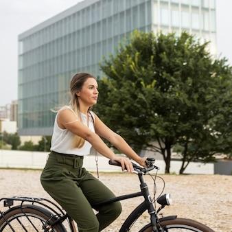 Donna di vista laterale che guida la sua bici