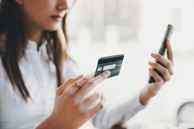 Vista laterale delle mani della donna che tiene una carta di credito di plastica mentre in un'altra mano uno smartphone dell'interno.