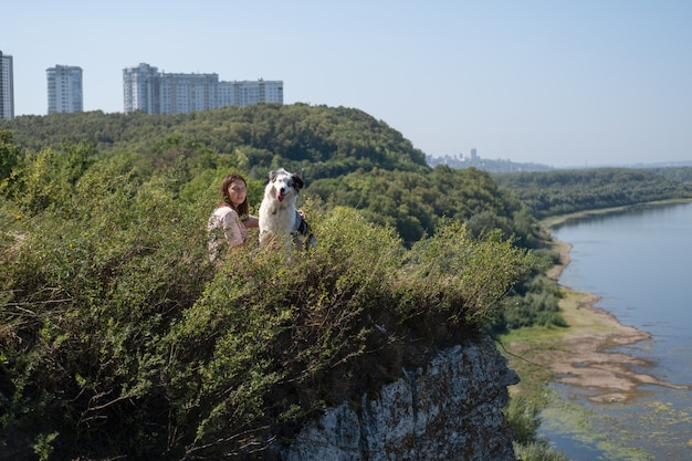 La vista laterale della donna si siede con il cane di merle blu del pastore australiano sulla sponda del fiume, estate. amore e amicizia tra uomo e animale. viaggia con animali domestici.