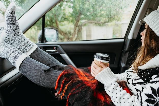 Donna di vista laterale che si siede in una macchina con una tazza di caffè