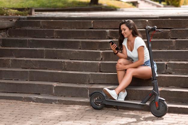 Vista laterale della donna sui gradini utilizza lo smartphone accanto allo scooter