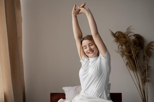 Vista laterale di una donna che si estende a letto dopo il risveglio. una bella mattinata dopo un sonno tranquillo e profondo. concetto di risveglio