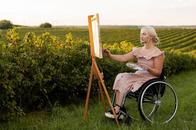 Vista laterale della donna nella pittura su sedia a rotelle all'aperto