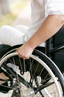 Vista laterale della donna in sedia a rotelle