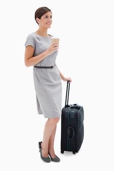 Vista laterale della donna con caffè e sacchetto wheely