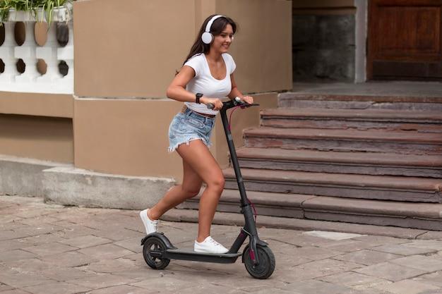 Vista laterale della donna con le cuffie in sella allo scooter
