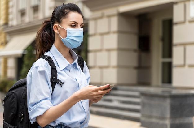 Donna di vista laterale con maschera medica che guarda lontano mentre si tiene il suo telefono