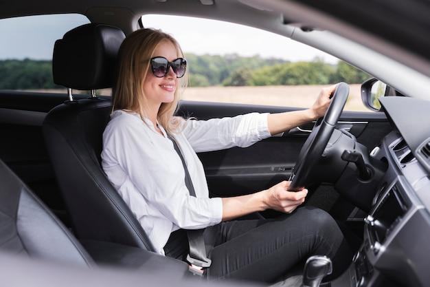 Vista laterale della donna con la guida di occhiali da sole