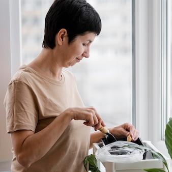 Vista laterale della donna con cazzuola che pianta i semi in vaso con terreno