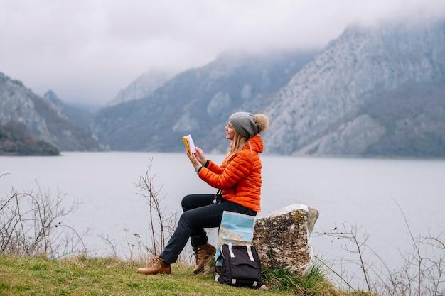 La vista laterale della donna in un cappello di lana e un cappotto arancione legge un libro in natura con mappa e borsa