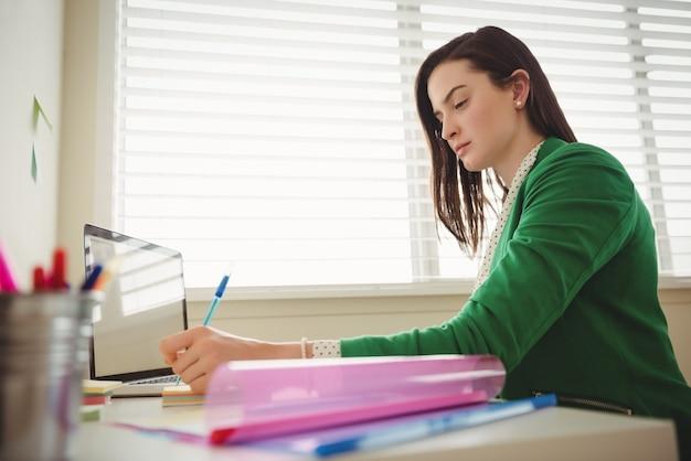 Vista laterale della donna che scrive mentre è seduto al tavolo