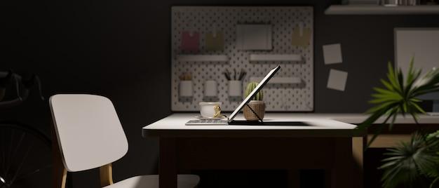 Vista laterale dello spazio di lavoro di notte con arredamento della sedia del laptop sulla parete grigia ufficio scuro di sera