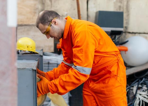 Vista laterale del lavoratore in uniforme con guanti e occhiali protettivi