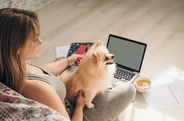 Vista laterale del concetto di casa di lavoro - ragazza con laptop, documenti e lavoro di tè dal suo soggiorno con il suo cane.
