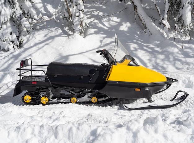 Vista laterale della motoslitta gialla sulla neve al giorno pieno di sole di inverno