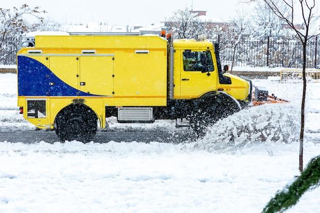 Vista laterale di uno spazzaneve giallo che pulisce la neve su un viale principale della città.