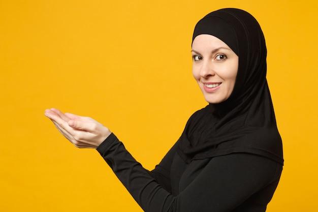 Vista laterale giovane donna musulmana araba in abiti neri hijab tenere in mano un'area di lavoro vuota isolata sulla parete gialla, ritratto. concetto di stile di vita religioso della gente.