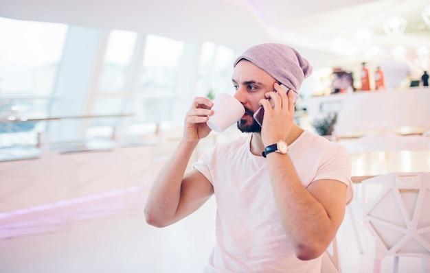 Vista laterale del giovane uomo barbuto, vestito in cardigan grigio, seduto al tavolo di legno rotondo in caffetteria con interni moderni ed è in possesso di smartphone