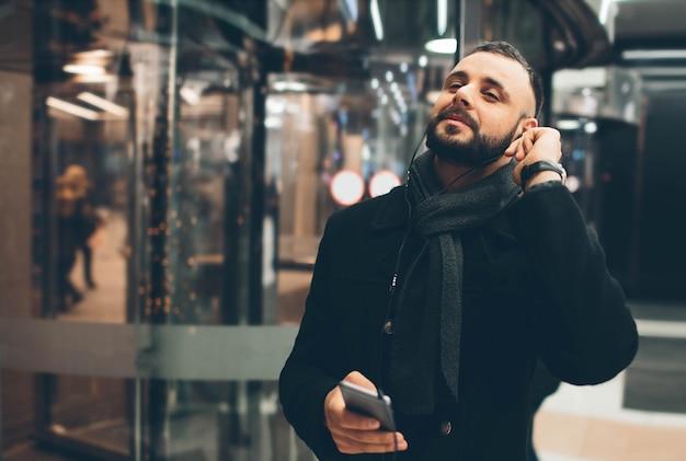 Vista laterale del giovane uomo barbuto, vestito abbigliamento casual, è in piedi sulla strada e utilizza uno smartphone.