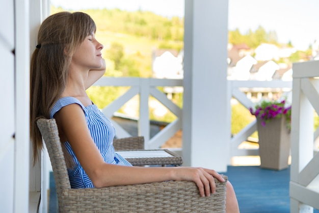 Vista laterale di giovane bella donna che riposa sull'aria fresca che si siede sul portico a casa.