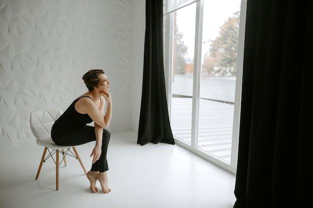 Vista laterale della giovane bella donna seduta sulla sedia e guardando nella finestra