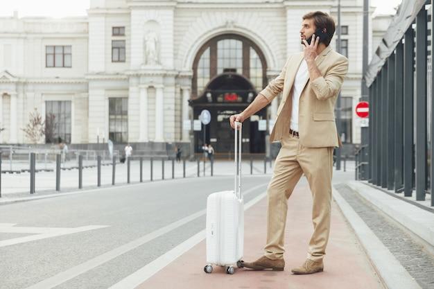 Vista laterale del giovane uomo d'affari in abito beige alla moda parlando sul cellulare mentre si sta in piedi sulla fermata dei mezzi pubblici con la valigia bianca