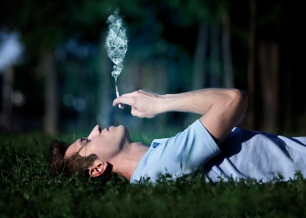 Vista laterale di giovane ragazzo spensierato sdraiato sull'erba