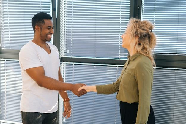 Vista laterale della giovane donna d'affari caucasica che ha conversazione con un collega maschio afroamericano vicino alla finestra. stretta di mano di uomini d'affari alla conferenza d'affari dopo una negoziazione riuscita.