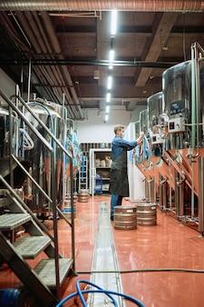 Vista laterale del giovane birraio maschio contemporaneo in abiti da lavoro in piedi da un enorme serbatoio di acciaio con birra mentre si scelgono le impostazioni sul pannello di controllo