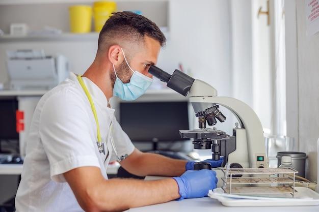 Vista laterale del giovane assistente di laboratorio maschio dedicato con guanti di gomma e maschera facciale utilizzando il microscopio.